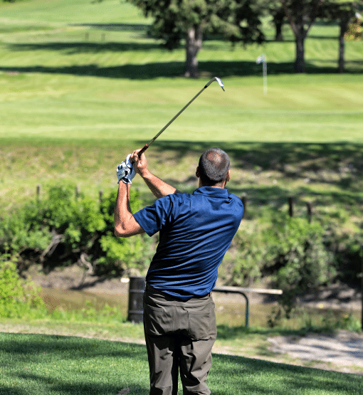 Golfer teeing off at hole 6 wearing Kingswell Swag.